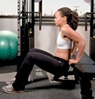 Chelsea Cooper demonstrates a tricep bench dip. - Copyright – Stock Photo / Register Mark