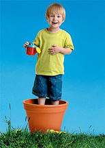 A young boy standing in a flower pot and holding a toy watering can. - Copyright – Stock Photo / Register Mark