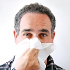 Man blowing his nose into a tissue. - Copyright – Stock Photo / Register Mark