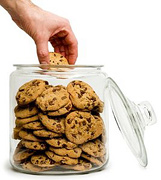 A man's hand removing a chocolate chip cookie for the cookie jar. - Copyright – Stock Photo / Register Mark