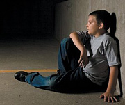 A depressed preteen sitting with his back to a wall. - Copyright – Stock Photo / Register Mark