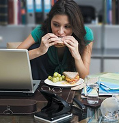 Woman eating at her work desk. - Copyright – Stock Photo / Register Mark