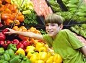 Boy reaching for a red pepper in super market. - Copyright – Stock Photo / Register Mark