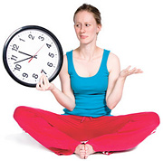 A woman dressed for exercising holding a clock in one hand. - Copyright – Stock Photo / Register Mark