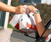 A fast food worker hands two bags of food to a customer at a drive-thru window. - Copyright – Stock Photo / Register Mark