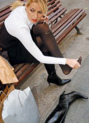 Woman who has been wearing high heeled boots massaging her foot. - Copyright – Stock Photo / Register Mark