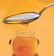 A spoon pouring honey into a bottle shaped like a bear. - Copyright – Stock Photo / Register Mark