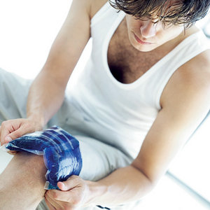 Man icing his injured knee. - Copyright – Stock Photo / Register Mark