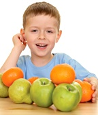 Young boy with various fruits in front of him.