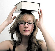 Young woman balancing large book on top of her head. - Copyright – Stock Photo / Register Mark