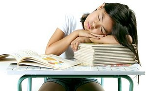 Little girl asleep on a stack of books on her school desk. - Copyright – Stock Photo / Register Mark