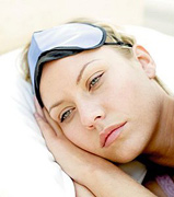A woman lying awake in bed. - Copyright – Stock Photo / Register Mark