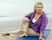 Elderly woman doing yoga on beach. - Copyright – Stock Photo / Register Mark