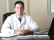Doctor of Chiropractic at his desk. - Copyright – Stock Photo / Register Mark